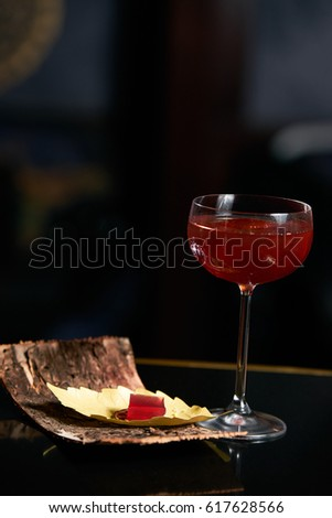 Fresh branded red alcoholic cocktail with a small bottle for alcohol and a red marmalade snack on a black stone bar counter.  Concept of alcoholic and non-alcoholic bar beverage. #617628566