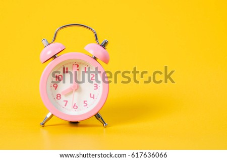 Vintage pink alarm clock on yellow background with copy space. #617636066