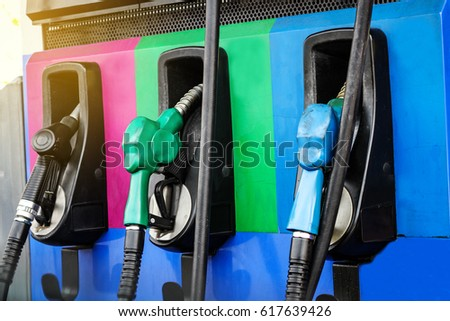 Three colors of fuel nozzle at gas station #617639426