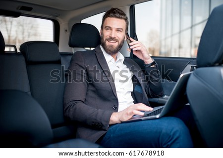 Handsome businessman talking with phone sitting with laptop on the backseat of the car #617678918
