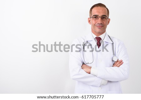 Studio shot of Persian man doctor with arms crossed against white background #617705777