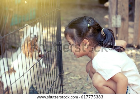 Cute asian little girl is playing with dog in cage #617775383