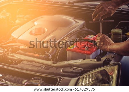 Car service ,fitting a car battery with wrench / soft focus picture