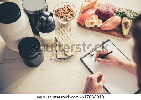 Cropped image of handsome young sportsman making notes while preparing sport nutrition in kitchen at home Royalty-Free Stock Photo #617836010