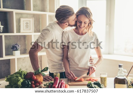 Beautiful young couple is talking and smiling while cooking healthy food in kitchen at home. Man is kissing his girlfriend in cheek #617837507
