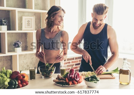 Beautiful young sports people are talking and smiling while cooking healthy food in kitchen at home #617837774