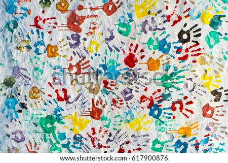 A lot of bright colorful handprints of children and adults on a white street wall. Chefchaouene, Morocco #617900876