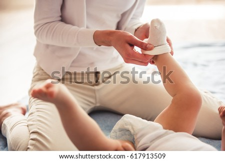 Cropped image of beautiful mom putting on her cute baby socks #617913509