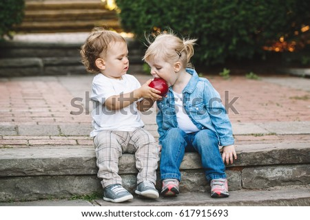 Group portrait of two white Caucasian cute adorable funny children toddlers sitting together sharing eating apple food, love friendship childhood concept, best friends forever Royalty-Free Stock Photo #617915693