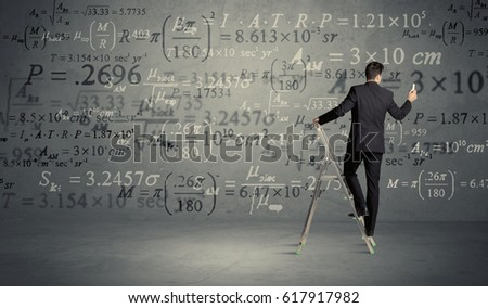 A businessman in elegant suit standing on a small ladder and writing numbers, calculating on grey wall background #617917982