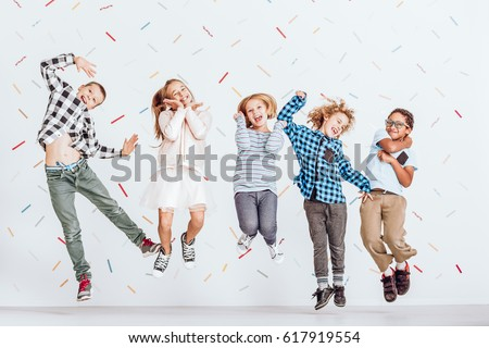 Happy group of kids jumping in a room with decorative tape on the wall #617919554