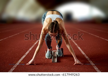 A young Caucasian girl athlete in gray leggings, reds and a short white top, in excellent sports uniform on a red treadmill in a covered sports arena prepares for the race and stands in pose of runner Royalty-Free Stock Photo #617949263