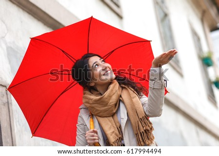 Portrait of beautiful woman with red umbrella #617994494
