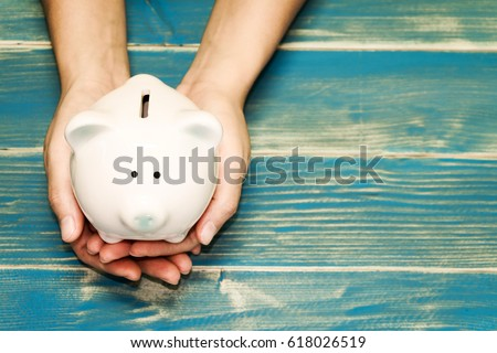 Women hold a pig bank on the vintage blue background, a saving money for future investment concept. Royalty-Free Stock Photo #618026519