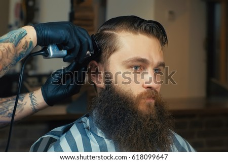 Handsome bearded man is looking forward while having his hair cut by hairdresser at the barbershop #618099647