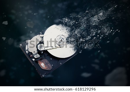 The old hard disk drive is disintegrating in space. Conception of passage of time and obsolete technology Royalty-Free Stock Photo #618129296