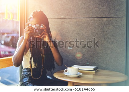 Young woman photographer taking picture for own collection and photo presentation on retro camera and sitting at table in coffee shop near promotional background for your advertising text message