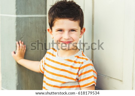 Outdoor portrait of a cute little boy standing against grey wall on a very sunny day, wearing grey and orange stripe tshirt #618179534