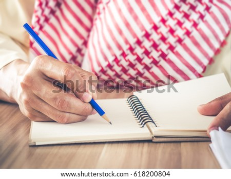 Arab businessman holding pen/pencil and writing on note book concept for business plan.