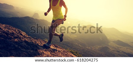 Young fitness woman trail runner running up at mountain top cliff edge #618204275