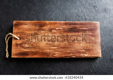 Rustic wooden cutting board on black stone background close up - rustic empty copy space for text, design element #618240434