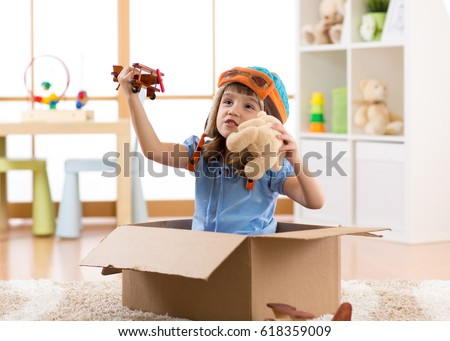 Kid child pilot flying a cardboard box in kid room Royalty-Free Stock Photo #618359009