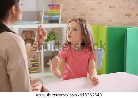 Young woman teacher and little girl on private lesson Royalty-Free Stock Photo #618362543