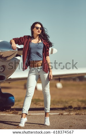 Pilot woman next to propeller of small private business plane outdoors in sunny day. Attractive young multi-racial Asian Caucasian sexy girl in jeans and shirt standing in full lenght at sport #618374567