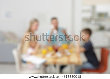 Blurred background of family having breakfast on kitchen