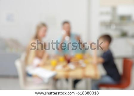 Blurred background of family having breakfast on kitchen