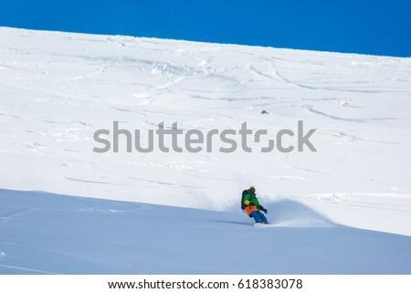 snowboarder snowboarding on fresh snow on ski slope on Sunny winter day in the ski resort in Georgia #618383078