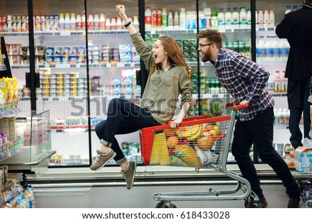 Happy couple having fun while choosing food in the supermarket. Young happy man pushing shopping cart with his girfriend inside Royalty-Free Stock Photo #618433028
