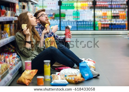 Portrait of a young funny hungry couple sitting on the supermarket floor and eating junk food Royalty-Free Stock Photo #618433058