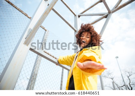 Picture of smiling african curly young lady wearing yellow coat walking outdoors. Looking at camera.