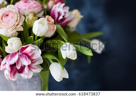 Flower arrangement with tulips and ranunculus on a white wooden floor. Spring flower arrangement in a vase #618473837