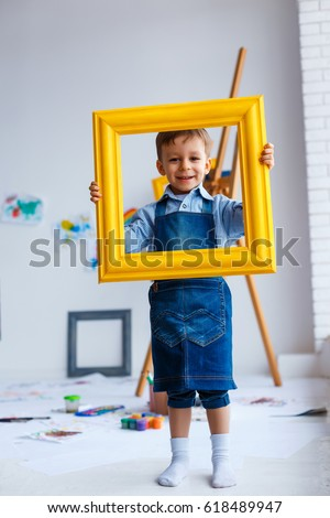 Cute, happy, white boy in blue shirt and jeans smiling and looking through yellow frame. Little child having fun in artist studio. Concept of early childhood education, happy family, parenting
