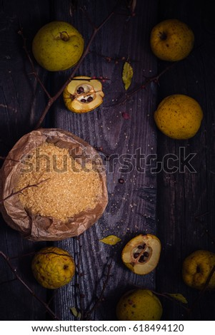 Fruits, twigs quince, sugar on a wooden table #618494120