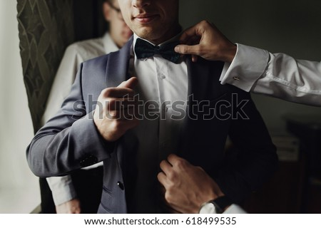 stylish groomsmen helping happy groom getting ready in the morning for wedding ceremony. luxury man in suit in room. space for text. wedding day. #618499535