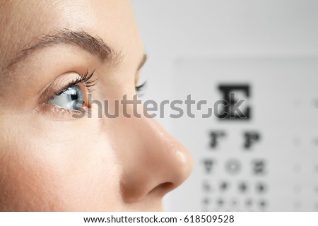 Young woman on eyesight test chart background Royalty-Free Stock Photo #618509528