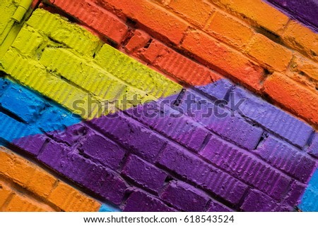 Abstract detail of brick wall with fragment of colorful graffiti, street art closeup. For backgrounds. Modern iconic urban culture youth, concept design