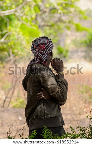 TAMBERMA VIL, TOGO - JAN 13, 2017: Unidentified Tammari the guy in the jacket turns away in the village. Tammaris are ethnic group of Togo and Benin #618552914