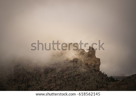 A rocky mountain top covered by mystic clouds. #618562145