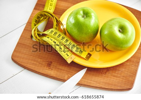 The concept of the diet. Green apple lying in the dish, centimeter  on wooden plate closeup #618655874