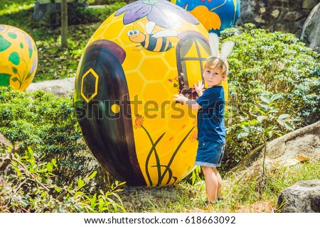 Nha Trang, Vietnam -15 March 2017: Cute little kid boy with bunny ears having fun with traditional Easter eggs hunt, outdoors. Celebrating Easter holiday. Toddler finding, colorful eggs. #618663092
