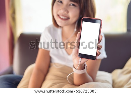 Asian woman looking at smart phone, reading message, sitting on sofa in living room #618723383