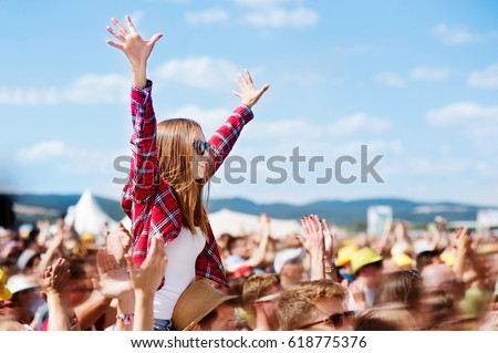 Teenagers at summer music festival enjoying themselves Royalty-Free Stock Photo #618775376