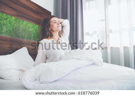 Pretty young woman on bed in modern apartment smiling and stretching after wake up #618776039