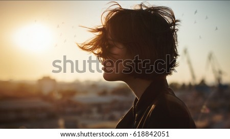 Melancholic beautiful portrait profile. Young girl, autumn mood, birds in the city sky. The port is abrasive against the background. Romantic affecting mood #618842051