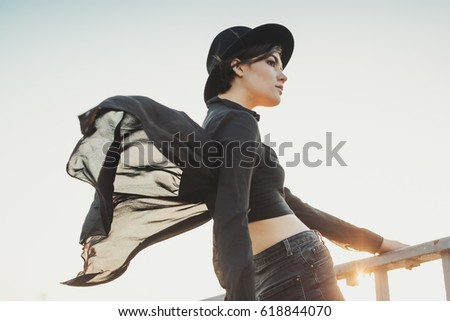 Beautiful lovely young stylish woman portrait. Black clothes, sky and sunset sun.  Big city Poets.  Bright orange sunset backlight Glares and flares. #618844070