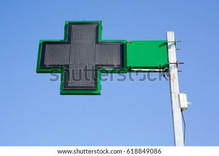 Pharmacy sign under blue sky with Green cross on a building #618849086